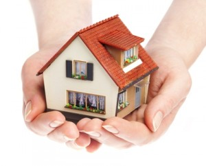 woman hands carrying a little house